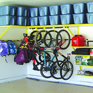 Bikes hung on a wall of a garage surrounded by organizational tools