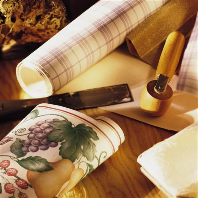 Rolls of wallpaper and tools need to put up wallpaper