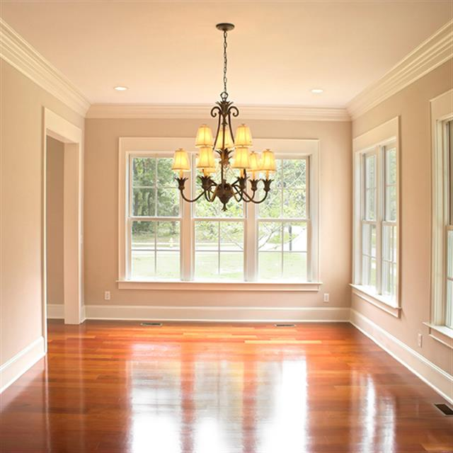 New crown molding and trim in a living room with wood floors and a chandelier