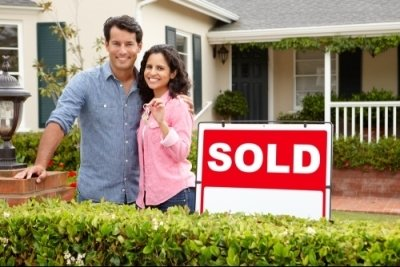 couple standing next to a sold sign in front of a house