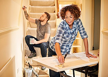 couple doing home renovations and painting together