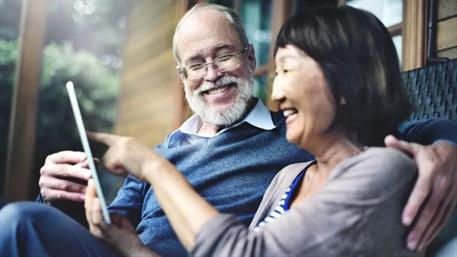 Man and woman laughing at a tablet