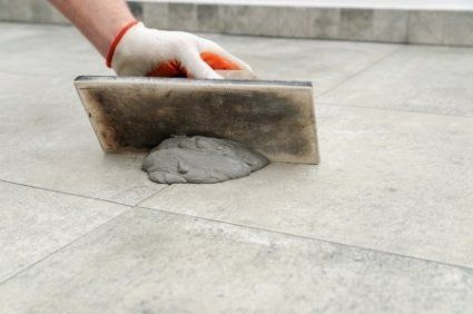 hand regrouting a floor